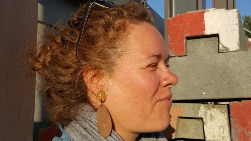 Inge Ohly bijohly, Schmuckdesignerin, weiße Frau mittleren Alters, von der Seite fotografiert, die lockigen, kurzen Haare sind mit einer hochgeschobenen Sonnenbrille zurückgehalten, sie kneift die Augen zusammen, lächelt und trägt ovale Holzohrringe