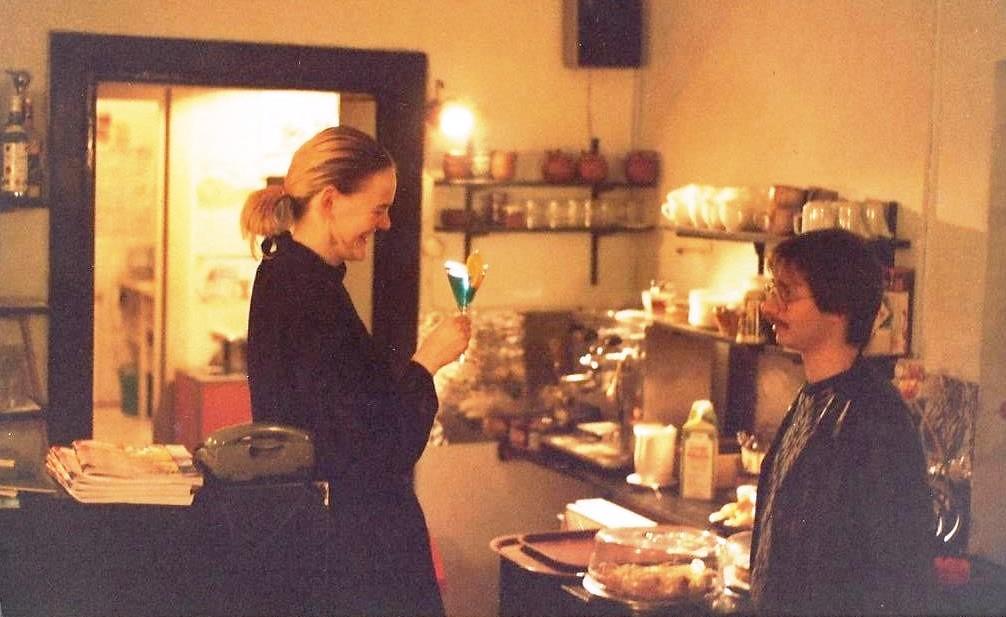 Unternehmerin sein - Ulla mit Cocktail und Gast im Café Cralle, ca. 1990, im Hintergrund Geschirr, Kaffeemaschine