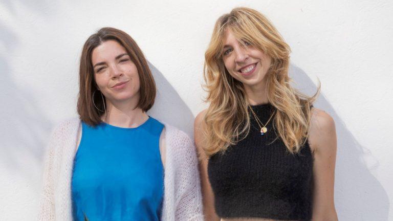 Knit Knit Gründerinnen: Zwei junge Frauen, eine mit glatten, halblangen dunklen Haaren, eine mit gewellten langen blonden Haaren lächeln, eine trägt ein blaues Top und eine helle Strickjacke, die andere ein schwarzes Top