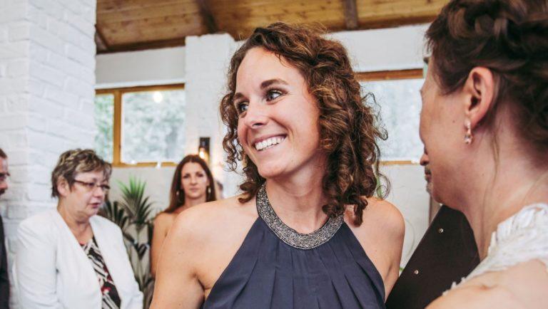 Elisabeth Mandl, Freie Rednerin, eine junge Frau mit schulterlangen, braunen gelockten Haaren in einem eleganten dunkelblauen Kleid lächelt nach links, um sie herum eine Festgesellschaft