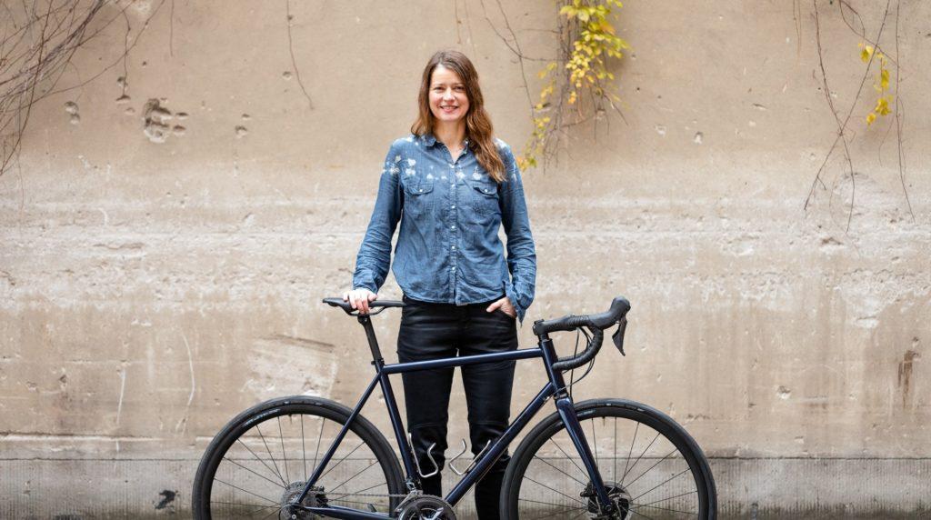 Eine junge Frau mit langen, gewellten braunen Haaren steht vor einer Hofwand und hinter einem schwarzen Rennrad. Sie lächelt direkt in die Kamera und trägt ein blaues Jeanshemd und schwarze Hosen.