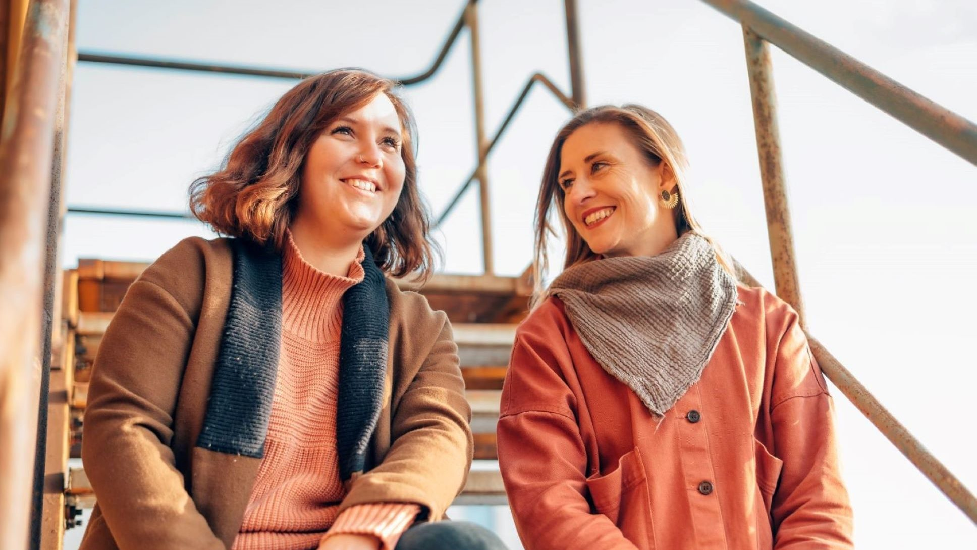Zwei junge Frauen lächeln, die linke Frau schaut dabei schräg nach oben rechts, sie hat schulterlange, gewellte, braune Haare, trägt eine dicke braune Jacke und einen Pullover in orange, die rechte Frau lächelt die linke direkt an, sie hat lange, glatte, blonde Haare, trägt einen Mantel in orange und ein graues Tuch um den Hals