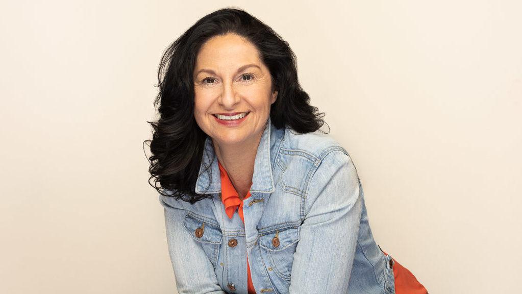 Anja Dittmeier, Coaching, eine ältere Frau mit langen, lockigen dunklen Haaren trägt dunkelroten Lippenstift, eine verwaschene Jeansjacke, darunter eine orange Bluse, sie steht leicht vorgebeugt und lächelt in die Kamera.