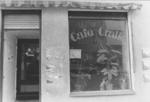 """s/w-Außenaufnahme eines Cafés. Im Schaufenster sind Grünpflanzen zu sehen, der Schriftzug am Fenster """"Café Cralle"""" in Serifenbuchstaben mit dicken Rundungen an den Buchstabenenden."""