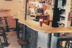 ein unregelmäßig geformter Holztresen, davor Barhocker, dahinter Geschirr, Kaffeemaschine.