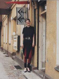 große, junge Person mit Pumphosenkleid, Leggings, Stulpen und Pumps steht lächelnd vor einem Eingang unter einem Schild, auf dem in spitzen, eckigen Buchstaben Café Cralle steht.