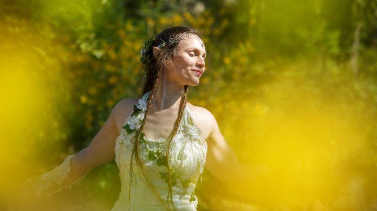 Entspannungsfee Anna Cuba: Frau mittleren Alters mit floralem Kleid und langen Zöpfen, steht mit geschlossenen Augen und ausgebreiteten Armen lächelnd im Sonnenlicht. Unscharf drumherum sind Büsche oder Bäume zu sehen, im Vordergrund am Bildrand unscharfe gelbe Flecken.